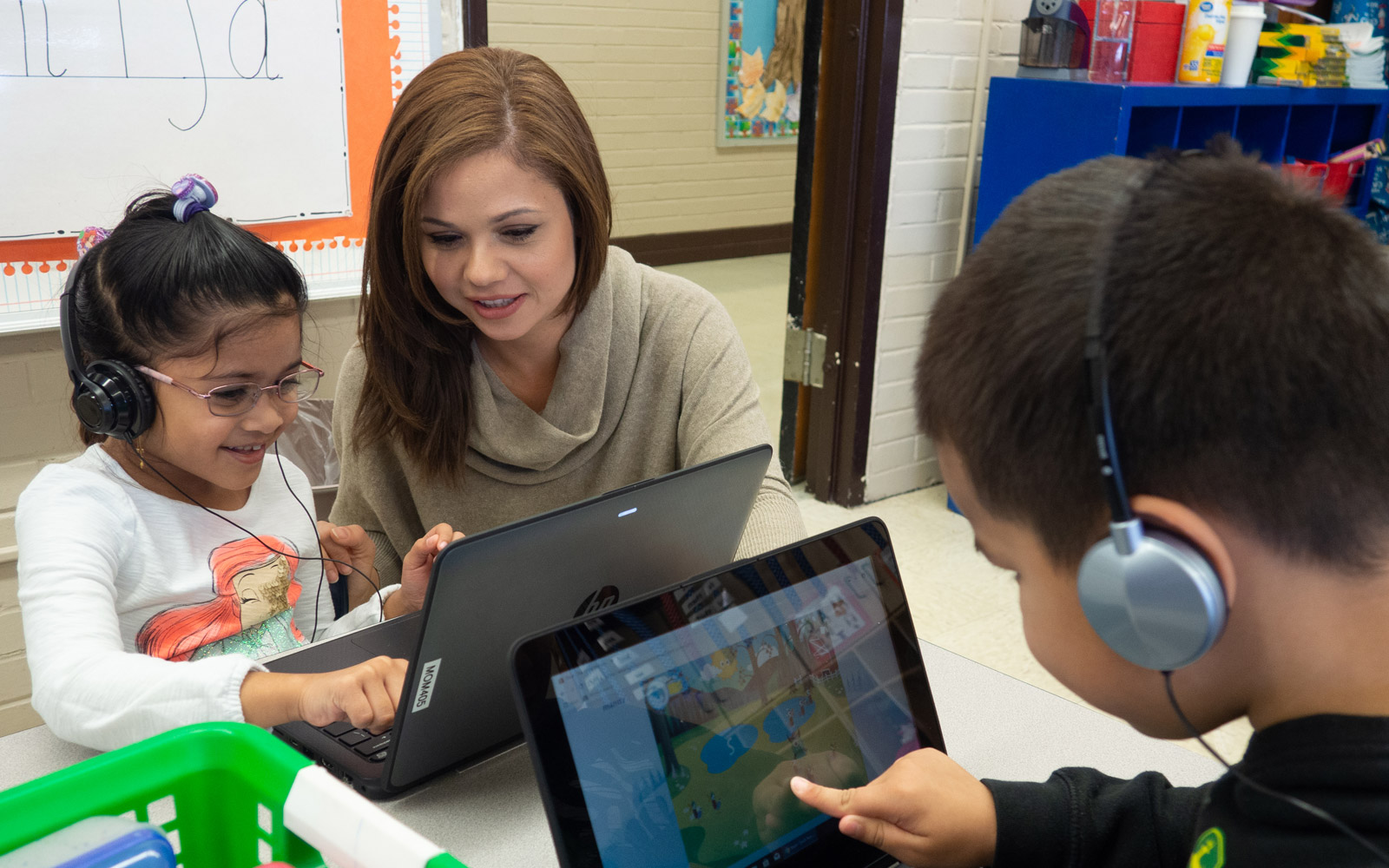 young female teacher working with elementary school girl and school boy wearing headphones and pointing at laptops